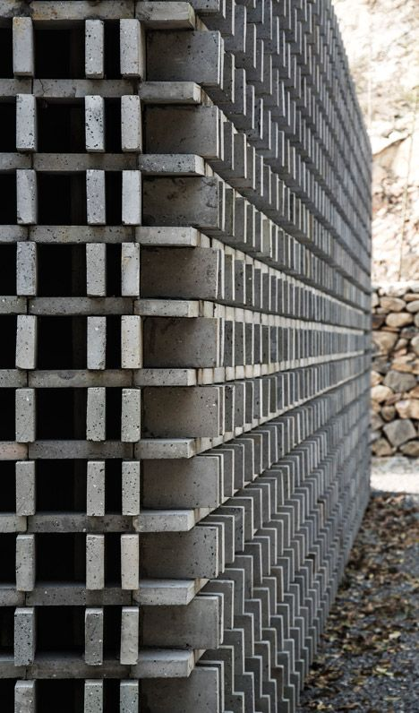 Bricks give a perforated facade to mountain building by Li Xiaodong