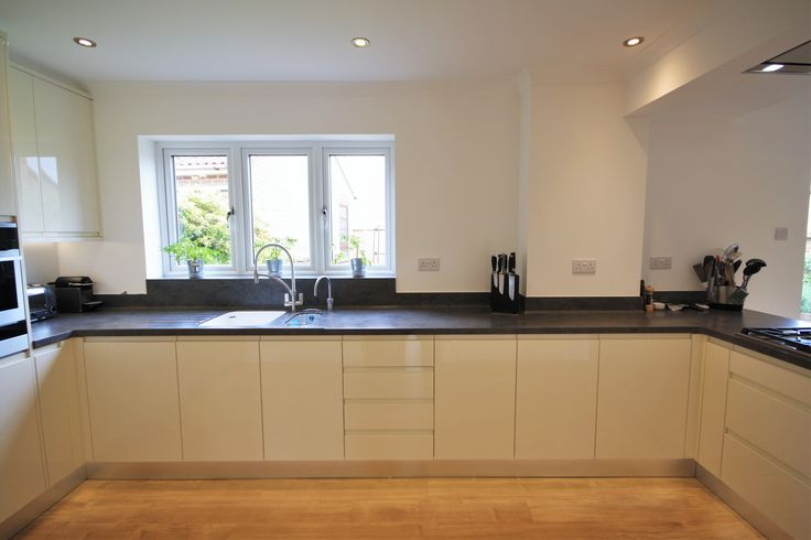 Gloss handless kitchen in Alabaster with a Corian worktop and up-stands in Lava Rock. Designed, supplied and installed by Kitchencraft, Essex.