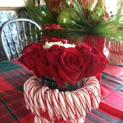 Saw this and gave it a try.  Candy canes surround a vase.  I used double sided tape and an elastic.  Tied red ribbon.  Bought floral foam.  Added water and some roses.