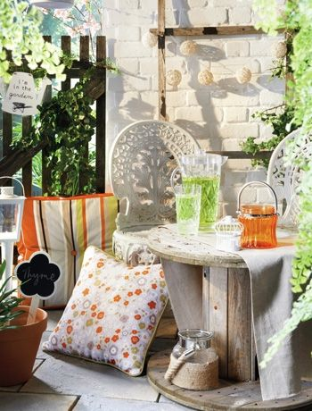 Painting brickwork white and choosing lighter paving slabs will really open up a small garden. (Furniture by Matalan).