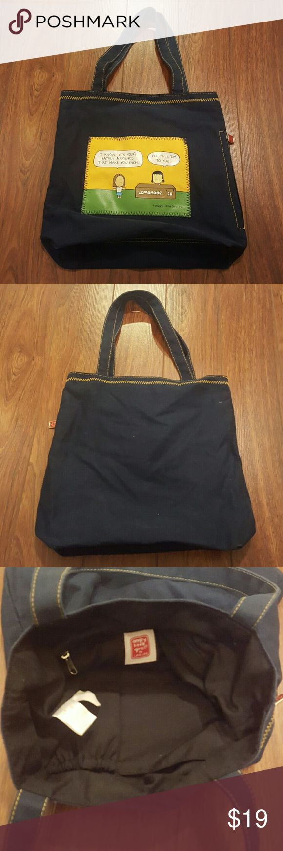 "Angry Little Girls Tote Navy blue eith yellow contrast stitching Open tote 1 exterior open pocket on front  1 exterior zippered pocket on side 1 interior zippered pocket 2 interior open pockets  Height: 13.5"" Width: 13.5"" Depth: 4"" Angry Little Girls Bags Totes"