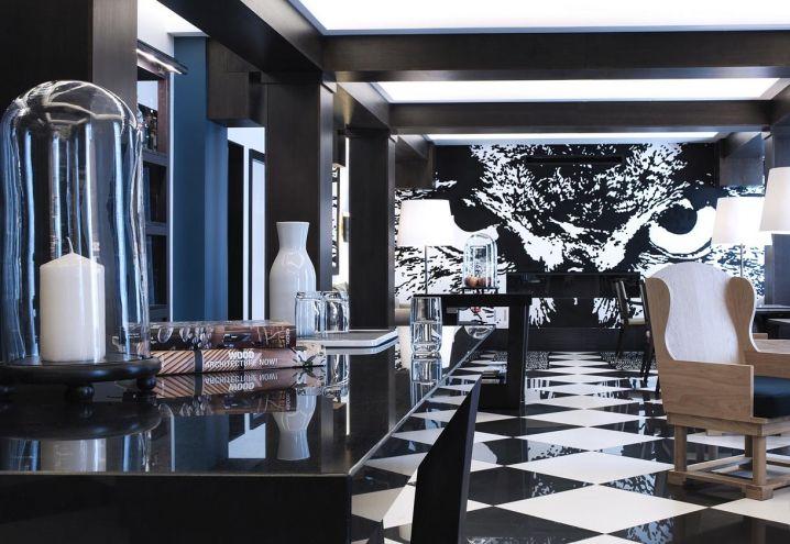 Pavimento a scacchi optical bianco e nero in pendant con il murale realizzato da Cyprien Chabert, raffigurante un'ipnotica civetta. Tutto questo nella hall al primo piano del The Chess Hotel di Parigi