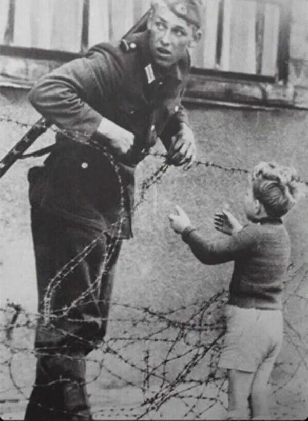Un soldato tedesco dell'est aiuta un bambino a scavalcare il neonato Muro di Berlino, 1961. Non ci è dato sapere la fine dei protagonisti di questo scatto. Qualcuno sostiene che il coraggioso soldato sia stato freddato da un cecchino sovietico, qualcuno ancora più pessimista dice che sia stato freddato persino il bambino. La versione più ottimistica sostiene che il piccolo si sia ricongiunto alla sua famiglia e che il soldato sia stato rimosso dall'incarico, ma che sia fortunatamente…