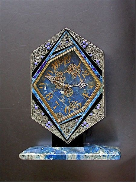 A French Art Deco desk clock, with a case in silver, lapis, and onyx, and set with marquesite, made circa 1925. The dial is predominantly blue embellished by asymmetrical angular geometrical figures. The time is indicated by gilt metal moon hands on a gold-painted Arabic chapter ring. The lapis base is marked France. The nickel Swiss 15 jewels movement is driven by a spring in a spring barrel and is of eight day-duration.