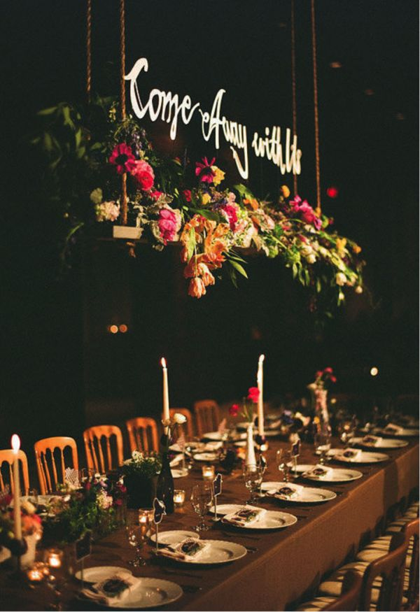 Calligraphy signs are all the rave for ceremony decor, so why not add them to a hanging centerpiece at the reception? The flower boxes above this wedding table complement the low centerpieces well on their own. But a simple phrase written in elegant script adds a more personal detail to this charming rustic event.