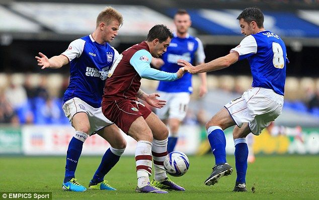 Double up: Danny Ings tries to hold off pressure from Ipswich Town's Luke Hyam (left) and Cole Skuse (right), in Burnley 1-0 away win.