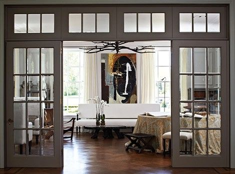 Glass French Doors Like Windows Separate The Living Room From A Large Foyer While Still Letting Light Flow Freely Between Rooms
