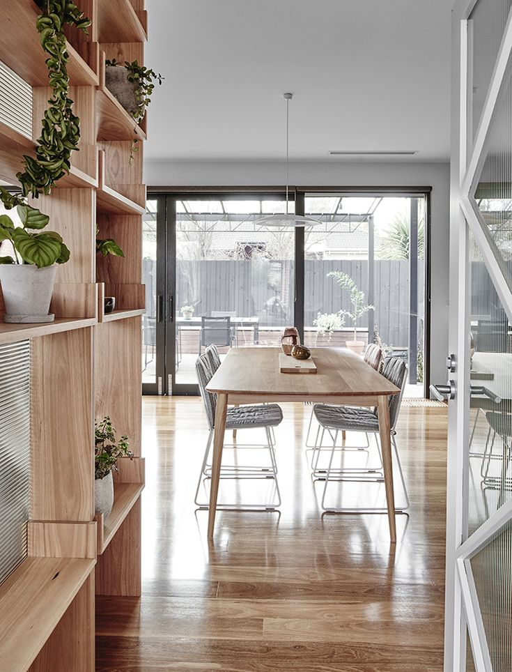 Dining area with natural wood dining table and white chairs, shelving, and plants