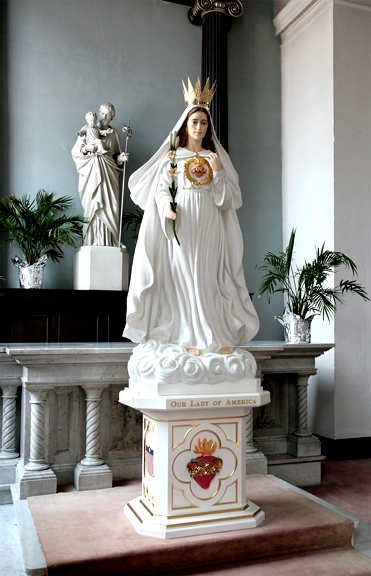 "The Blessed Virgin Mary, as she appeared to Sister Mary Ephrem (Mildred Neuzil). The Blessed Virgin Mary wishes to be honored in the National Shrine of the Immaculate Conception at Washington D.C. as ""Our Lady of America."" Our Lady says that if this is done, the United States of America would turn back toward morality and the shrine would become a place of ""wonders."""