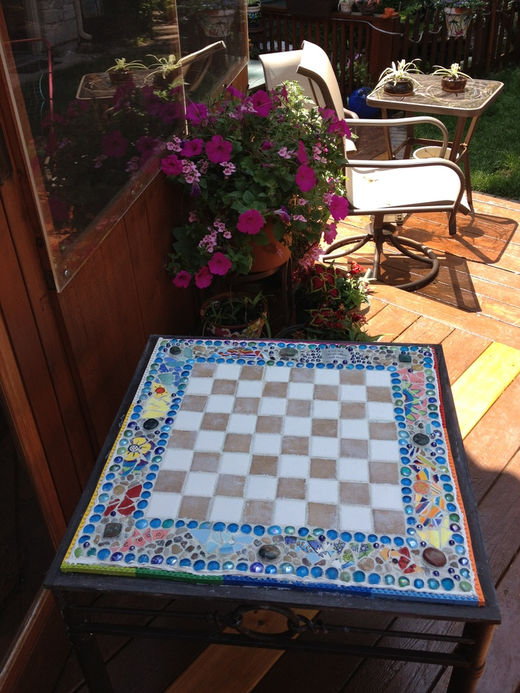 Checkers table made with tiles and mosaic edge.