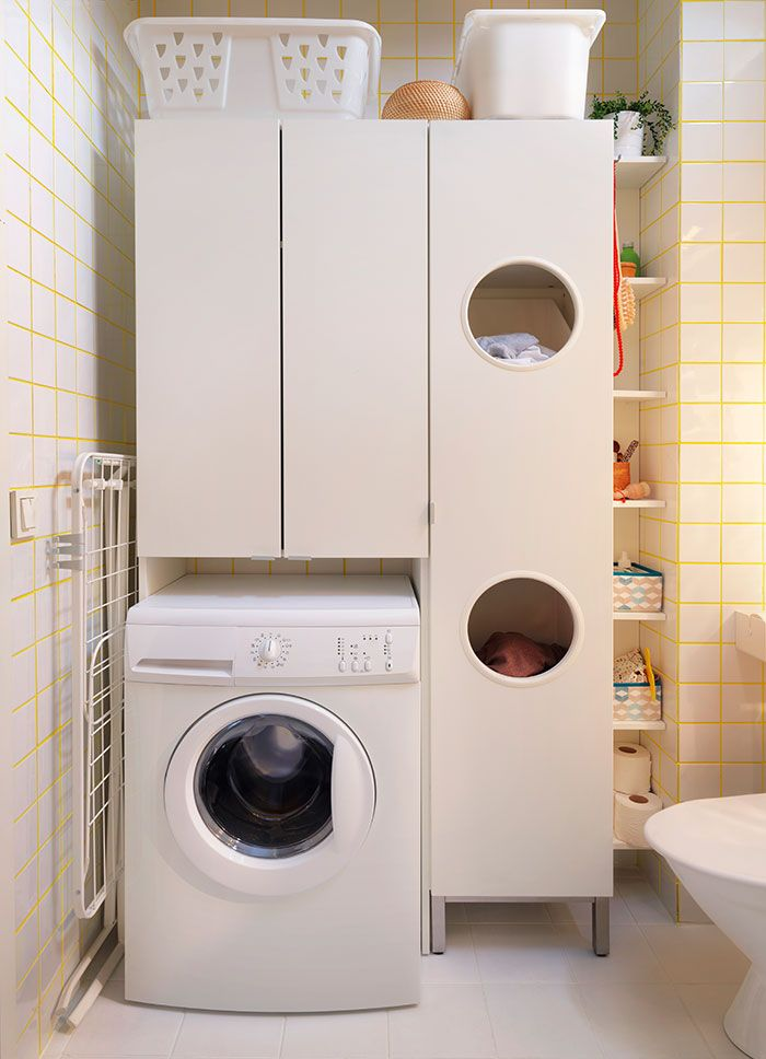 Laundry area in a bathroom with a washing machine and white cabinets with doors