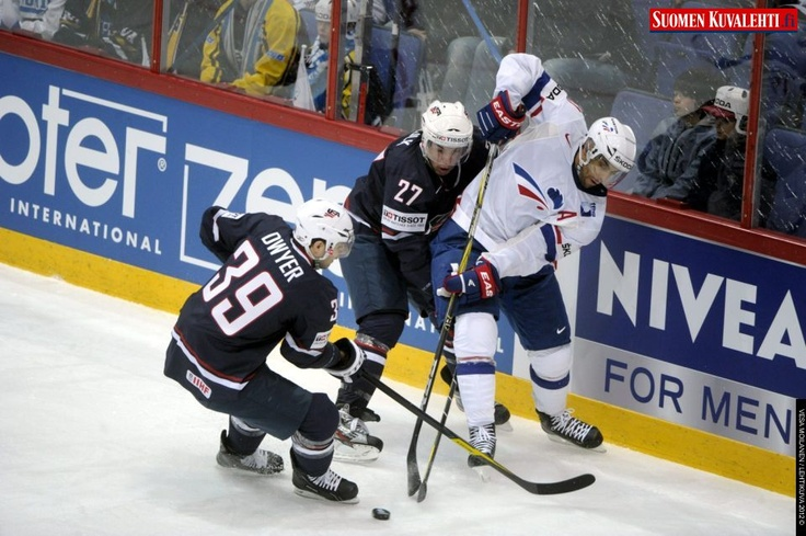 Patrick Dwyer (L) and Justin Falk of USA stop Pierre-Edouard Bellemare of France (R) during the game USA vs France, the opener of the 2012 IIHF Ice Hockey World Championships in Helsinki