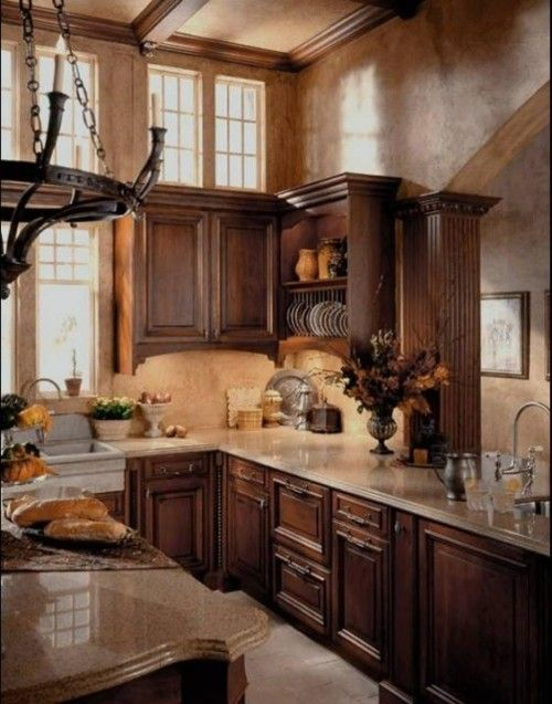 A beautiful and classic European-style kitchen with wood cabinets and  granite countertops (via