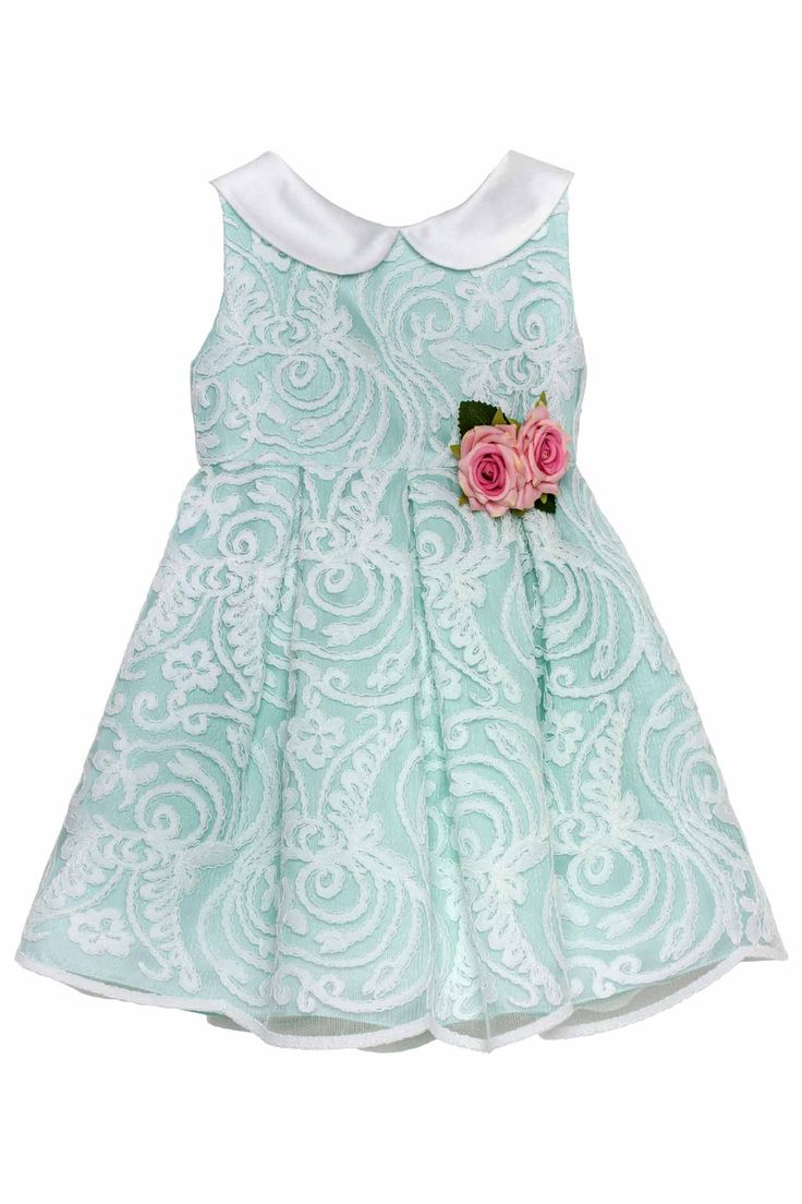 Dress with sleeveless bodice in precious ivory embroidered tulle with green lining and ivory silky collar. The wide pleated skirt is embellished at the waist by a removable handmade brooch made of two pink roses and leaves.