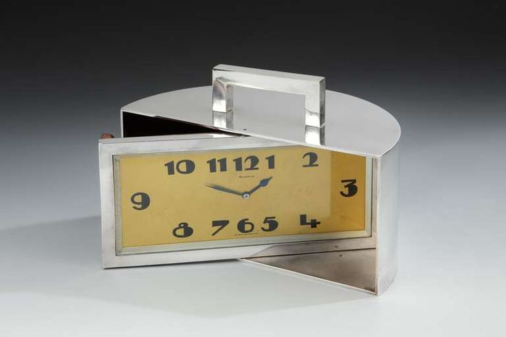 Art Deco Demilune Clock or Trinket Box, 1930. A fabulous and unusual Art Deco demilune mantel or desk clock, the heavy nickeled bronze mechanical movement clock with angular top handle, with wide, stylized Art Deco clock face and numerals, rotating to reveal a hidden wood lined trinket or cigarette box behind. (hva)