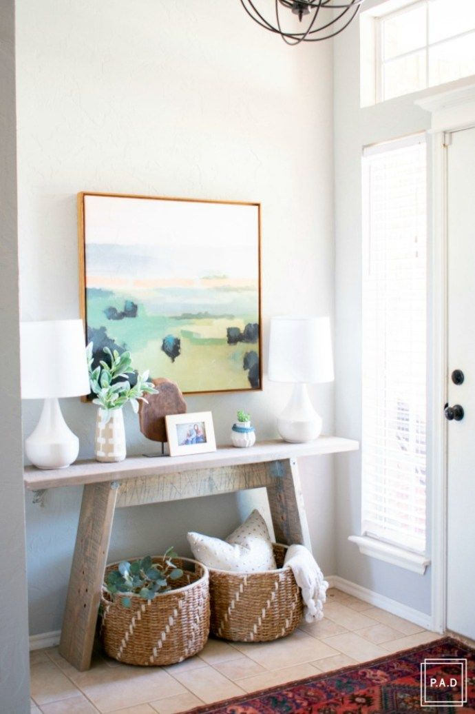 Welcome to our Spring Home Tour: See how we transformed our home with just a few simple changes, console table with framed art canvas. white lamps, vintage rug and decorative baskets under a orb chandelier create an inviting entryway.