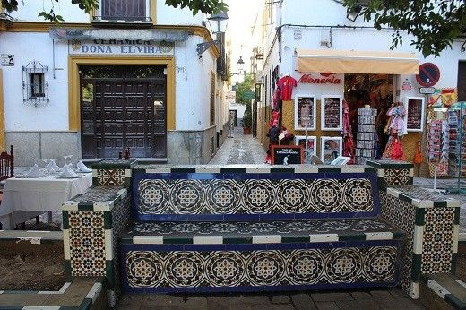 This is a very nice mosaic bench in Seville, Spain. You can also find a narrow street ( callejuelas in Spanish word) in the background (middle) of this image. At the right side is a souvenir store, where you can buy souvenirs of all kinds from postcards to travel guides, fridge magnets, shirts, etc. At the left side a ceramic shop. - My Scholarship entry - A 'place' I have visited - Spain - WorldNomads.com