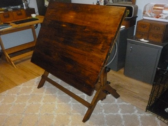 Very heavy, very sturdy. Perfect for a loft ! The wear on the piece is great! Push pin holes, knife cuts,, wear on the cast iron and even spots where the architect left his cigarette to long.. A truly great piece of history! Would make a great desk, standing desk, or dining table. Pictures are part of the description. Im happy to answer questions or provide more pictures. Great industrial drafting table with a dark wood finish. Great mix of wood and metal. This is such a nice table. These…