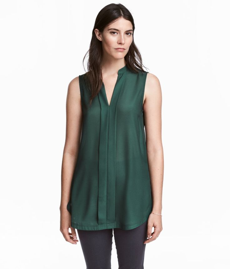Check this out! CONSCIOUS. Sleeveless blouse in airy woven fabric. Small stand-up collar, V-neck at front with decorative pleats, and yoke at back with pleat. Rounded hem with slits at sides. Polyester content is partly recycled. - Visit hm.com to see more.