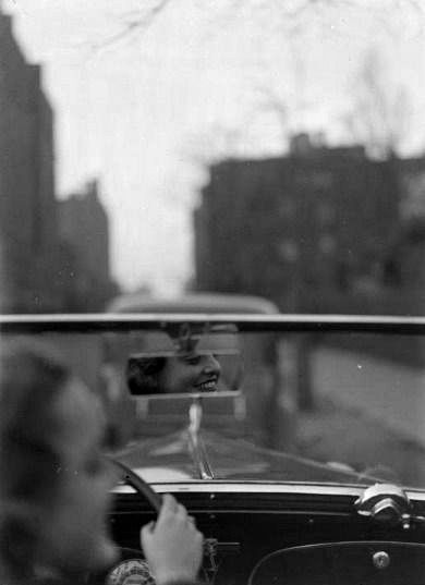 by Martin Munkacsi, Reflection of woman driving in rear view mirror, 1937