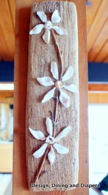 Find a flat piece of wood to use as a canvas. Then, find some broken clam shells to use as flower petals and tiny whole shells to use for the centers. After laying out the flower designs, hot glue them directly to the driftwood and add some wood for the stems.