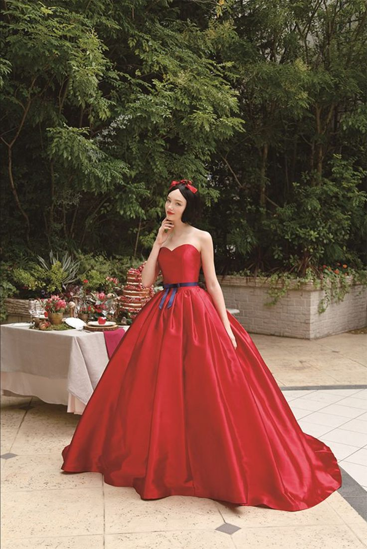Bright red snow white inspired strapless wedding ballgown with thin black belt and red ribbon in her hair // If you've ever wished upon a star to look like a princess, then Disney's collaboration with Japanese wedding company Kuraudia Co. is your dream coming true! Kuraudia's new range of 14 bridal gowns is inspired by 6 classic Disney princesses - Belle from Beauty and the Beast, Ariel from The Little Mermaid