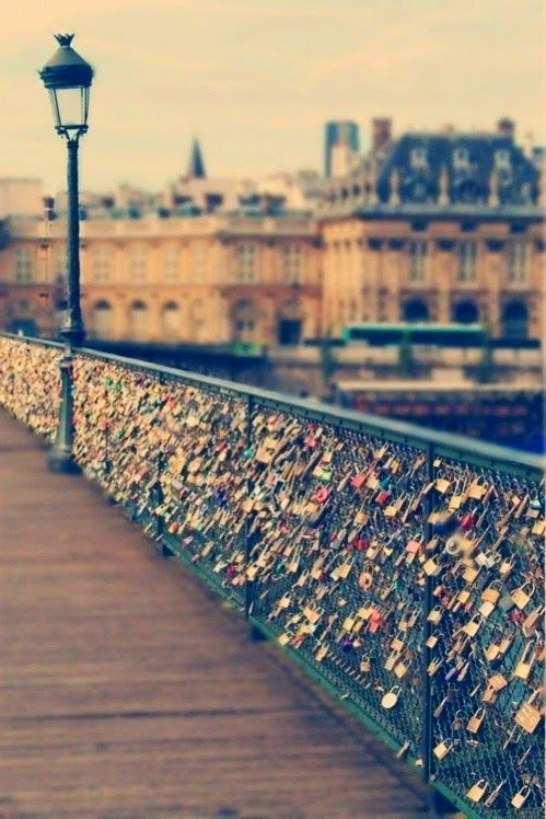 Love Lock Bridge in Paris. Lovers carve their initials in a padlock, attach it to the bridge, and throw away the key.