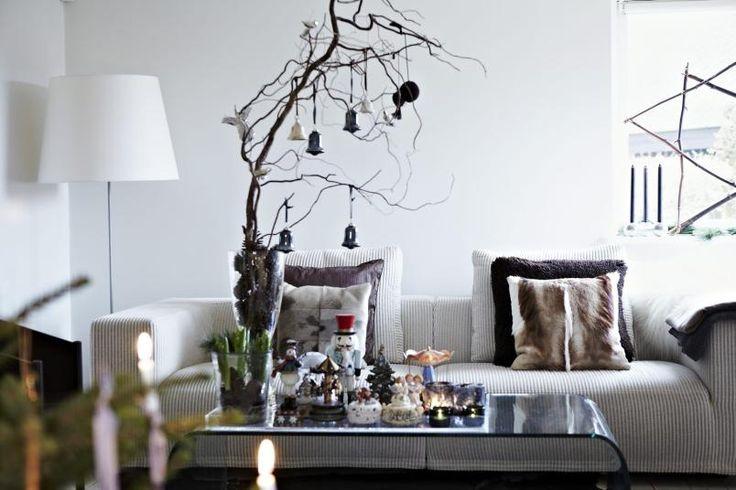 FINURLIG STEMNING. En samling avsmå karuseller står på et plastbrettpå stuebordet sammen med telysog vaser med julegrønt og greiner.Noen av karusellene spiller musikk,noen er antikke og noen er kitsch.Sofabordet i bøyd glass er fra CasaShop, sofaen er fra Eilersen.