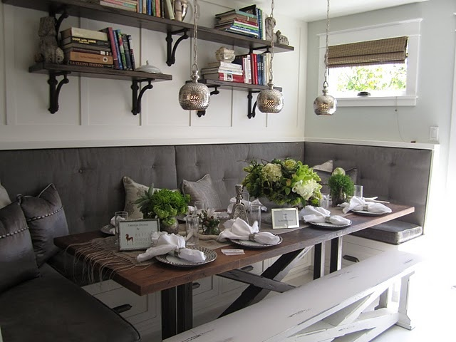 Love the color of the cushions and pillows against the white walls.  Perfect little breakfast nook.