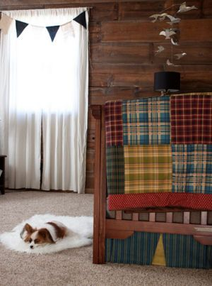 A rustic baby boy nursery design with a homemade, plaid crib quilt, a DIY bird baby mobile and many other crafts projects