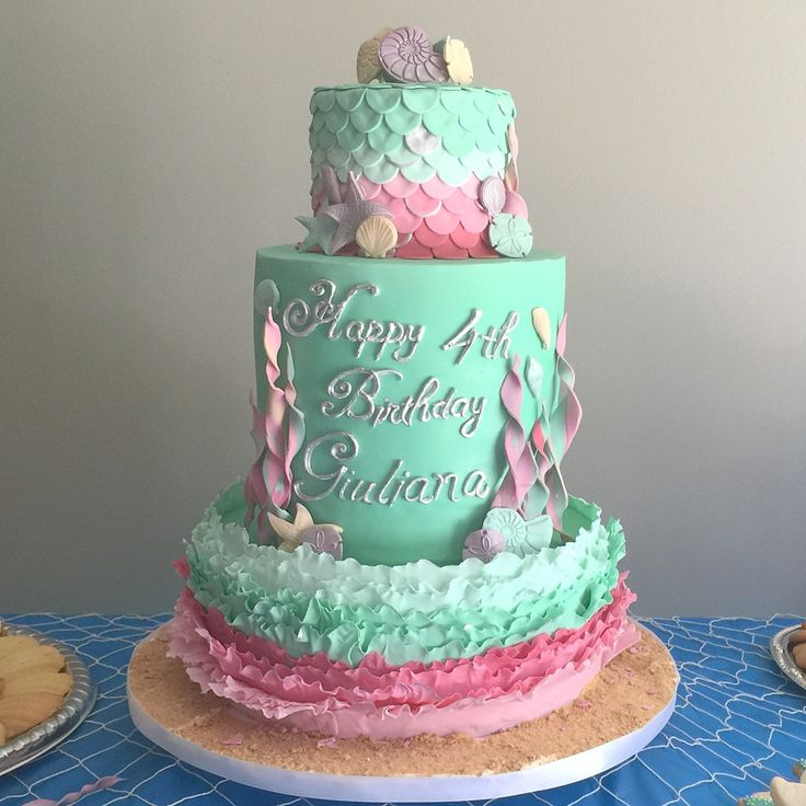 Mermaid under the sea birthday cake in pink and light green. Birthday cake is accented with sugar decorations resembling waves, seaweed and seashells. Cake created for a 4th birthday by www.lanasdoughdelights.com