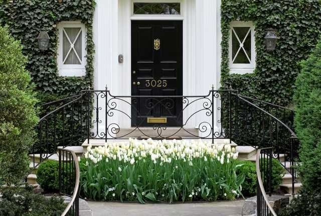 Cluster of white tulips + ivy on brick + black front door + non-lacquered brass door hardware