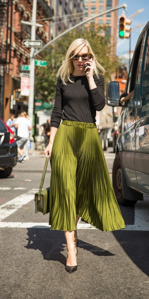 A green pleated skirt and black sweater