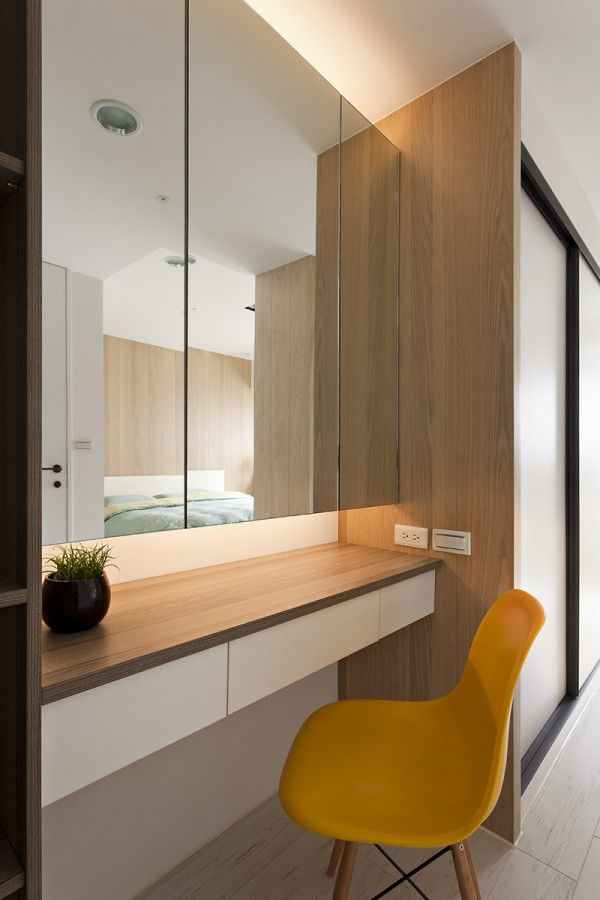 A pop of color in the bright yellow chair at the built-in vanity adjacent to the wardrobe makes the bedroom feel even cheerier.