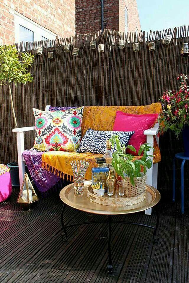 Kleine Boho Ecke auf dem Balkon mit bunten Kissen und Teetisch