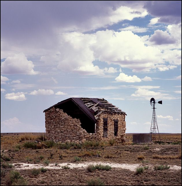 An abandoned stone house with a tin roof sits on a ranch in the New Mexico desert along US-55 south of Santa Rosa, NM
