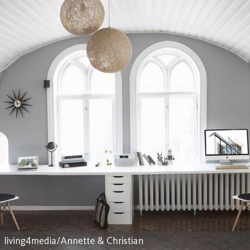 Dieser Arbeitsplatz für Zwei wirkt dank der runden Decke, den hellen schlichten Möbeln und viel Tageslicht offen und gemütlich. Die weißen Eames-Chairs…