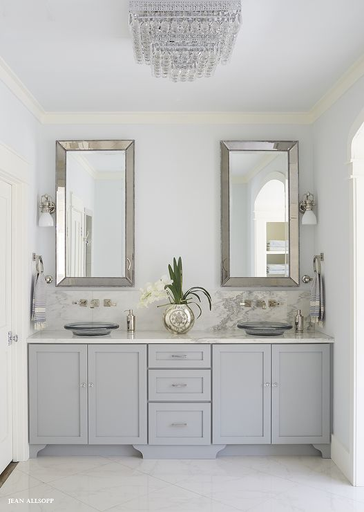 Fabulous gray bathroom features a gray dual vanity adorned with glass knobs paired with an Alabama White Marble countertops lined with round gray glass vessel sinks under faucets lined on an Alabama White Marble backsplash under Restoration Hardware Venetian Beaded Mirrors illuminated by 1920s Factory Sconces.