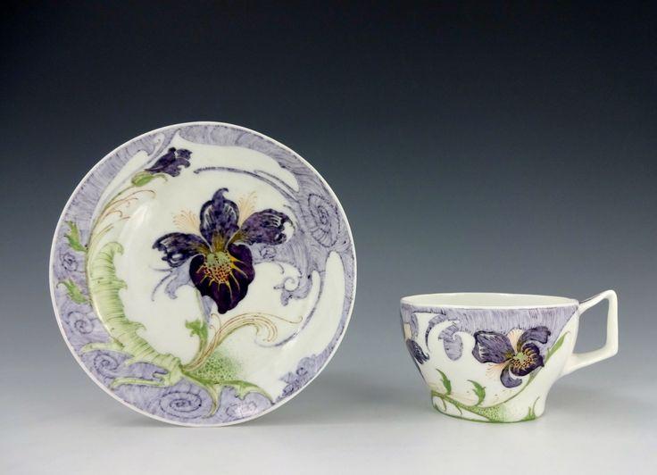 Een ronde kop en schotel van eierschaal porselein, model 68 en 22, beschilderd met paarse orchideeën. Gemerkt met het fabriek stempel, het schilders monogram en werkorder nummer 441, gefabriceerd in 1911 . Kopje is 5 cm hoog en schotel is 12 cm in diameter.