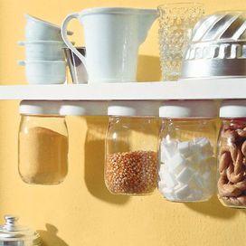 Volete sfuttare uno spazio insolito? Appendete i barattoli!Ecco come fareOccorrente: barattoli di vetro con tappi a vite di metallo o di plastica; mensola di legno; viti; cacciavite.Esecuzione: prima