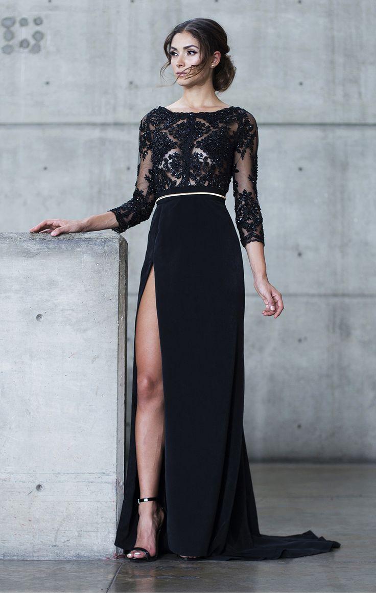Vestido negro elaborado de encaje bordado y pedrería, manga 3/4. Falda elaborada de toque de seda con apertura en un costado y ligera cauda. Detalle cinto metálico.