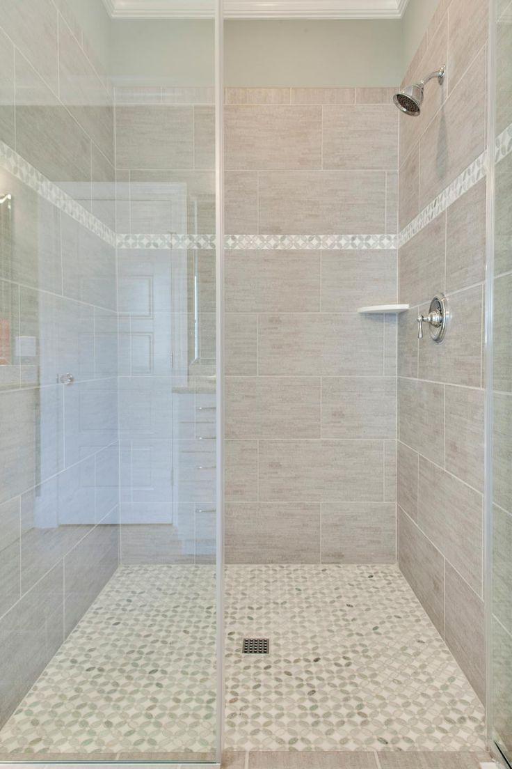 This spacious walk-in shower features large gray tiles with a textured look. Smaller tiles in a criss-cross pattern cover the floor and the thin accent strip on the shower wall.
