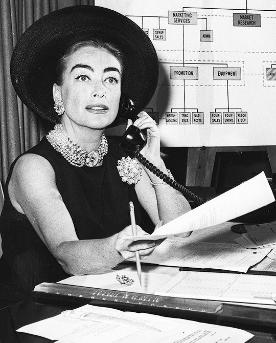 Joan Crawford photographed at her desk at the Pepsi-Cola company in New York, 1959. Joan was elected to Pepsi's board of directors after the death of her husband, Alfred Steele, who had been Chairman. She would serve on the board for the next 14 years.