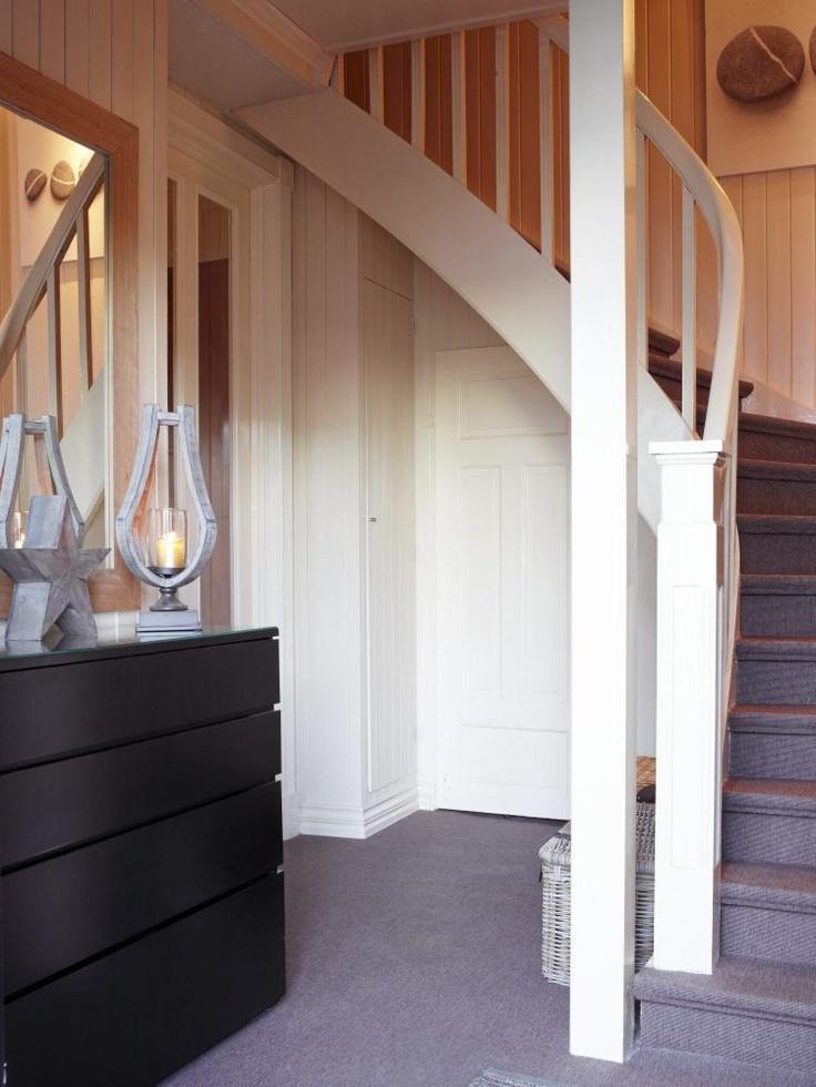 MYK INNGANG: Entreen har mykt vegg-til-vegg-teppe. Det gjør at trapperommet oppleves som en del av stuen som ligger rett ved. Den svartekommoden er en spesiallaget skokommodesom designet for å få plass til mange skopar i en liten gang.