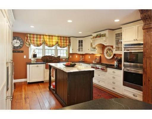 Kitchen with cream cabinets and burnt orange walls  MLS #71508075