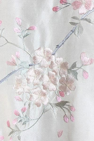 An embroidered satin kimono, Japanese for the European market, circa 1910, of ivory silk, with raised embroidered pastel toned blossom and roses, pink silk fringing to the wide sleeves