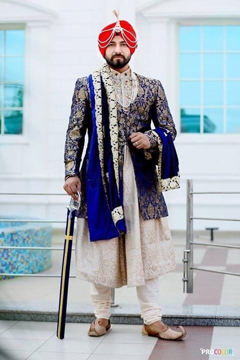 Groom Wear - Beige Kurta Churidaar with Blue Jacket | WedMeGood | Groom in a Beige Kurta Churidaar with a Royal Blue Brocade Jacket and a Velvet Saafa, Red Pagdi with a Kalgi #wedmegood #indiangroom #indianwedding #blue