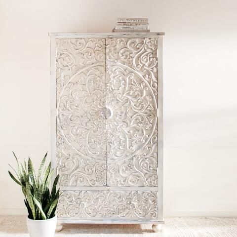 Truly something special, our versatile white armoire is hand carved by artisans of India into a sumptuous floral motif. Open the double doors to reveal twin adjustable shelves for clothing storage or to display your TV, and pull out the lower drawer for additional space.