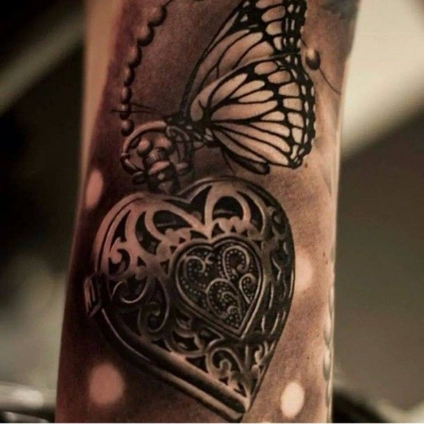 schmetterling tattoo mit Herzmedaillon als coole tattoo ideen arm