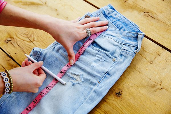 how to cut jeans into shorts with fringe | Step two: Fold the pants in half with button side facing up and pull ...